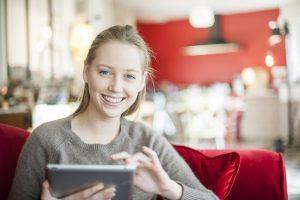 Junge Frau sitzt auf der Couch und benutzt ihr Tablet